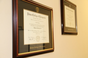 Fancy chiropractic degrees hanging on the wall